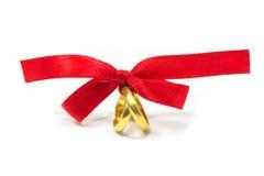 Gouden die ringen met rood lint worden gebonden royalty-vrije stock afbeelding