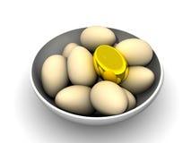 Gouden ei in een kom Stock Afbeelding