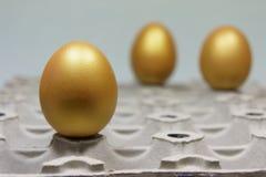 Gouden eieren op een eikarton Royalty-vrije Stock Afbeeldingen