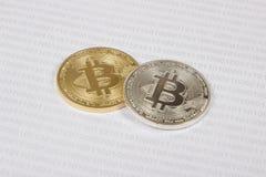 Gouden en zilveren bitcoin op de achtergrond van binaire code Royalty-vrije Stock Afbeeldingen