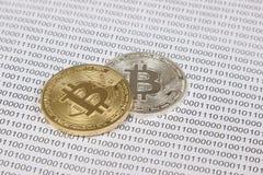 Gouden en zilveren bitcoin op de achtergrond van binaire code Stock Foto