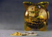 Gouden en zilveren muntstukken op een vage achtergrond met een geel transparant spaarvarken royalty-vrije stock foto