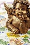 Gouden engelenbeeldhouwwerk op hoop van euro nota's Royalty-vrije Stock Afbeeldingen