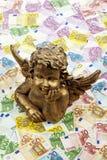 Gouden engelenbeeldhouwwerk op hoop van euro nota's Stock Foto's