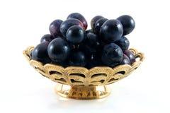 Gouden fruitschotel met zwarte gra Stock Afbeelding