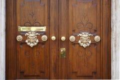 Gouden gekleurde hoofden als deurhandvat van een oude houten deur Royalty-vrije Stock Fotografie