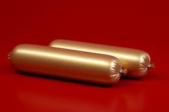 Gouden gekookte worst op bruin stock fotografie