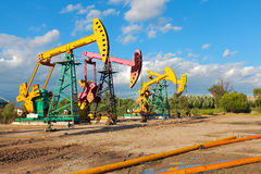 Gouden gele en roze Oliepomp van ruwe oliebroninstallatie Stock Foto