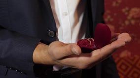 Gouden gift voor de vrouw die hij heeft gehouden van mens in een kostuum met gouden ringen in zijn hand de bruidegom houdt in zij stock video