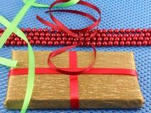 Gouden giftdoos met rode lintboog Stock Foto's