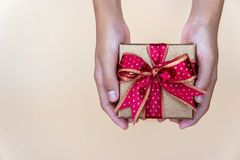 Gouden giftdoos met rode ribbow, die giftdoos voor speciale persoon op speciale dag geven stock fotografie