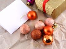 Gouden giftvakje met rode boog en Kerstmisballen die op oud document worden geplaatst Royalty-vrije Stock Afbeeldingen