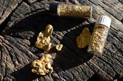Gouden goudklompjes en gouden vlokken in flesjes op hout als achtergrond royalty-vrije stock foto