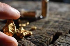 Gouden goudklompjes op hout als achtergrond stock fotografie