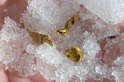 Gouden goudklompjes op in openlucht genomen sneeuw Royalty-vrije Stock Afbeeldingen