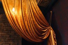 Gouden groot gordijn op bakstenen muur Stock Fotografie