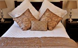 Gouden hoofdkussens op wit bed Royalty-vrije Stock Foto