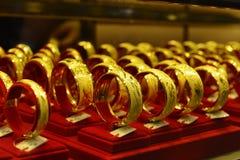Gouden juwelen in gouden winkelshowcase, Winkelvenster met heel wat juwelen Stock Foto