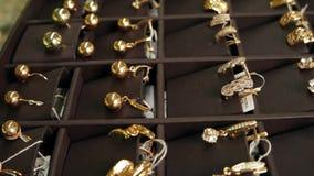 Gouden juwelen, Heel wat gouden die oorringen in het schot van de vensterschuif, voor verkoop, Juwelen op opslagvertoning wordt b stock footage