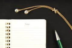 Gouden juwelen, pen en notitieboekje Royalty-vrije Stock Fotografie