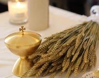 Gouden kelk en de oren van tarwe over een altaar in kerk stock fotografie