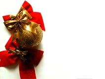 Gouden Kerstmisbal met rode bogen op witte achtergrond Royalty-vrije Stock Foto's