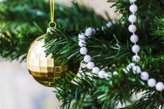 Gouden Kerstmisballen en rood licht op de groene boom Royalty-vrije Stock Fotografie