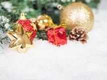 Gouden Kerstmisballen en ster en rode doos in de sneeuw Exemplaar en Stock Foto's