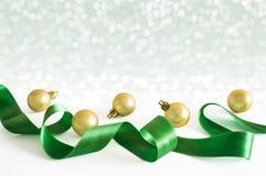 Gouden Kerstmisballen met groen lint met de winter van de lichtensneeuw Stock Fotografie