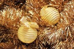 Gouden Kerstmisballen op een klatergoud Stock Fotografie