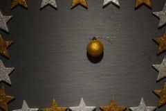Gouden Kerstmisornament op zwarte leiachtergrond Stock Fotografie