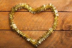 Gouden Kerstmisslinger in hartvorm op hout Stock Afbeeldingen