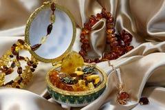 Gouden ketting met ambertegenhanger Baltische amber in Ceramische kist, amberhalsband en armband op een pastelkleur achtergrondsa Royalty-vrije Stock Foto