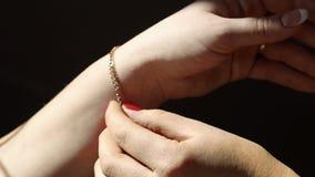 Gouden ketting op de hand van een vrouw Het meisje helpt om gouden juwelen op de hand van het meisje vast te maken stock footage