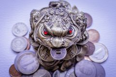 Gouden kikkerbeeldje op muntstukken Stock Foto