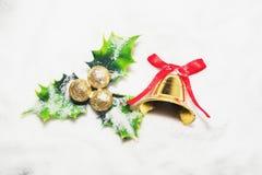 Gouden klok met rood lint en groen blad met ballen op witte sneeuw Stock Fotografie