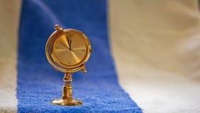 Gouden klok op geweven achtergrond Royalty-vrije Stock Foto's