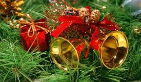 Gouden klokken tegen de boomtak van Kerstmis Royalty-vrije Stock Fotografie