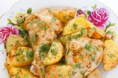 Gouden knapperige die huidkip in oven met aardappelwiggen wordt geroosterd stock afbeeldingen