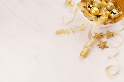Gouden kom met Kerstmissterren, ballen, linten op witte houten raad, exemplaarruimte Feestelijke Kerstmisachtergrond Stock Foto