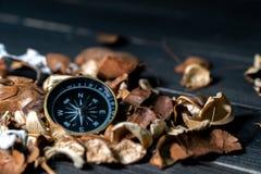 Gouden kompas gezet op droge bladeren op houten retro zwarte lijst stock afbeeldingen