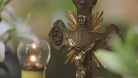Gouden kruisbeeld en kaars dichte omhooggaand stock video