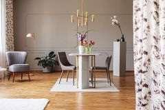 Gouden lamp boven eettafel en stoelen in grijs flatbinnenland met bloemen en leunstoel Echte foto royalty-vrije stock foto