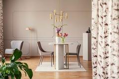 Gouden lamp boven stoelen en lijst met bloemen in elegant eetkamerbinnenland met installatie Echte foto stock afbeeldingen