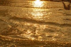 Gouden licht die van een watergolf bij het overzees nadenken en zand op zonsondergang Stock Afbeeldingen
