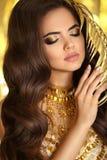 Gouden make-up Elegante donkerbruine vrouw manier juwelen Golvende hai Stock Foto's