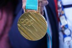 Gouden medaille van de XXIII Olympische de Winterspelen PyeongChang 2018 gewonnen door Olympische kampioen in Dames` Mogollen Per stock foto