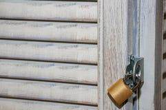 Gouden metaal gesloten hangslot op oude houten zonneblinden stock foto's