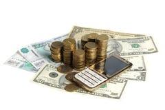 Gouden mobiele telefoon en een stapel muntstukken op de bankbiljetten Royalty-vrije Stock Afbeelding