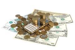 Gouden mobiele telefoon en een stapel muntstukken op de bankbiljetten Royalty-vrije Stock Foto's